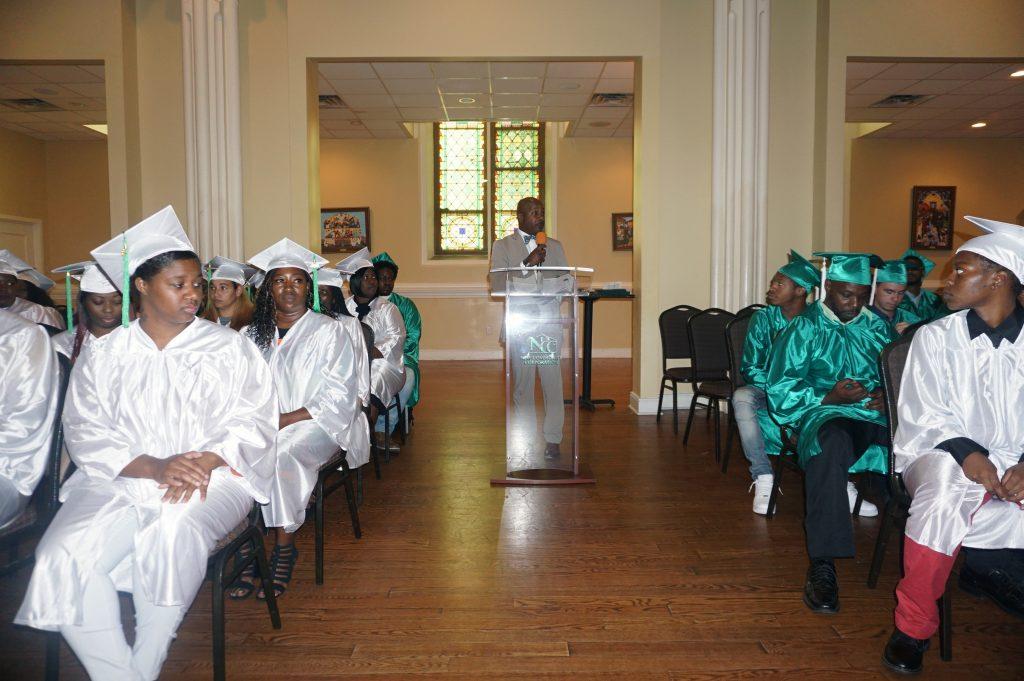 Wide shot of NCCTI graduates listening to director speak